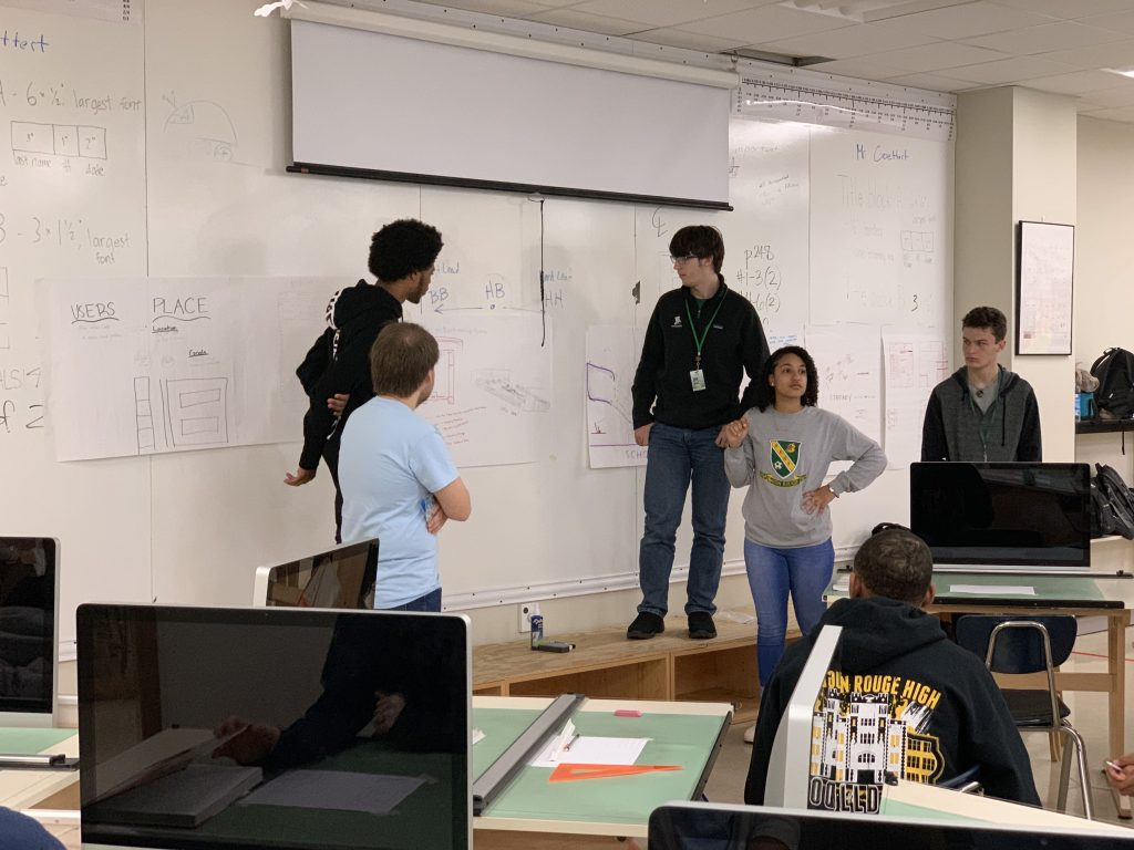 Students stand around board