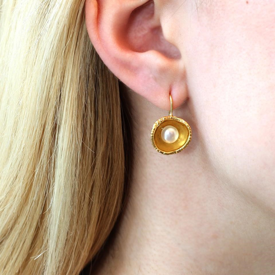 Gold oyster pearl earring hanging from ear