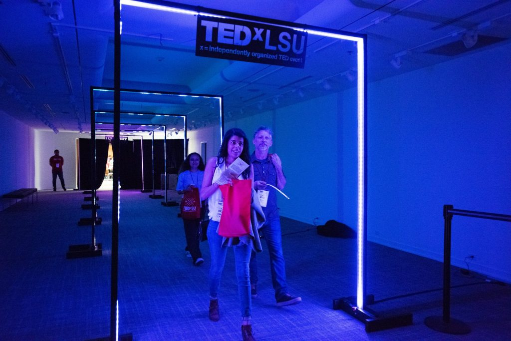 People walk into TedxLSU entrance, blue lights