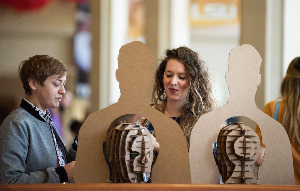 People study cardboard humanoid figures