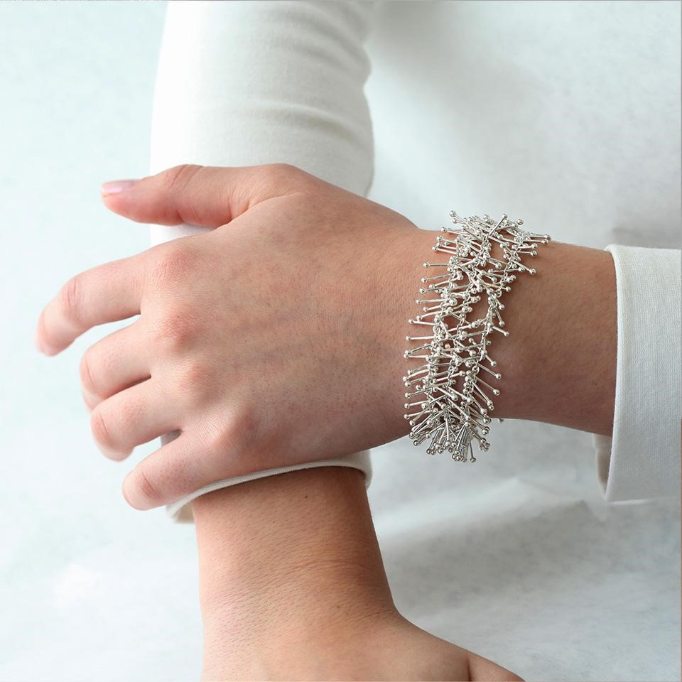 Silver feather bracelet on wrist