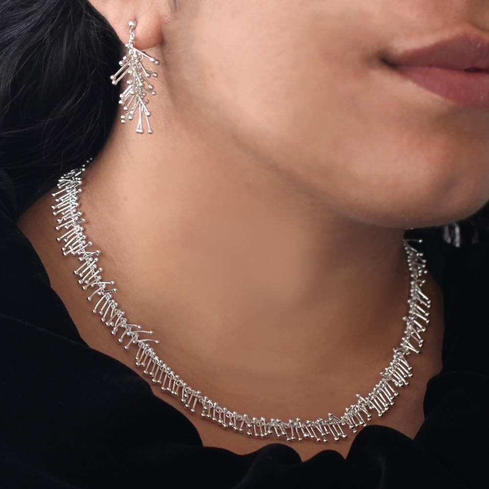 Silver chain necklace and earring on woman