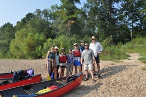 Group on sandy river back by red canoes