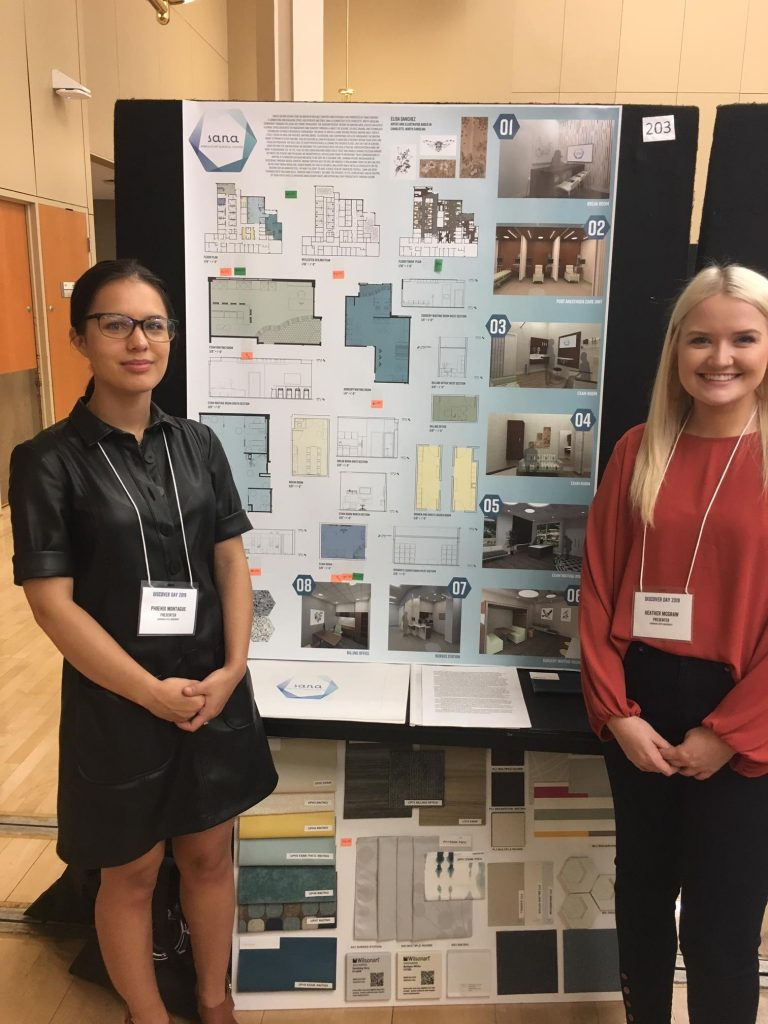 Two female students by research poster