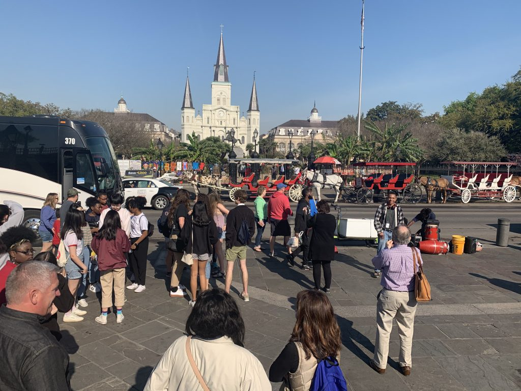 A group of people look toward white St Louis Cathedral.