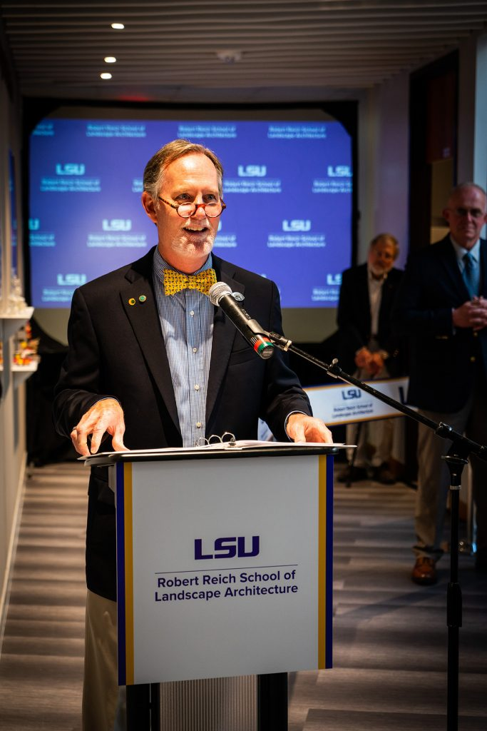 Man with yellow bow tie at podium