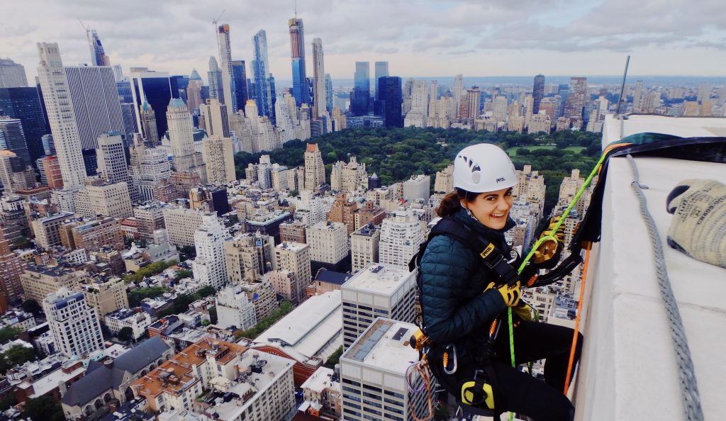 Elyse Marks scales skyscraper with view of New York City in background.