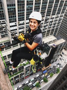 Woman repelling off building, tiny cars below