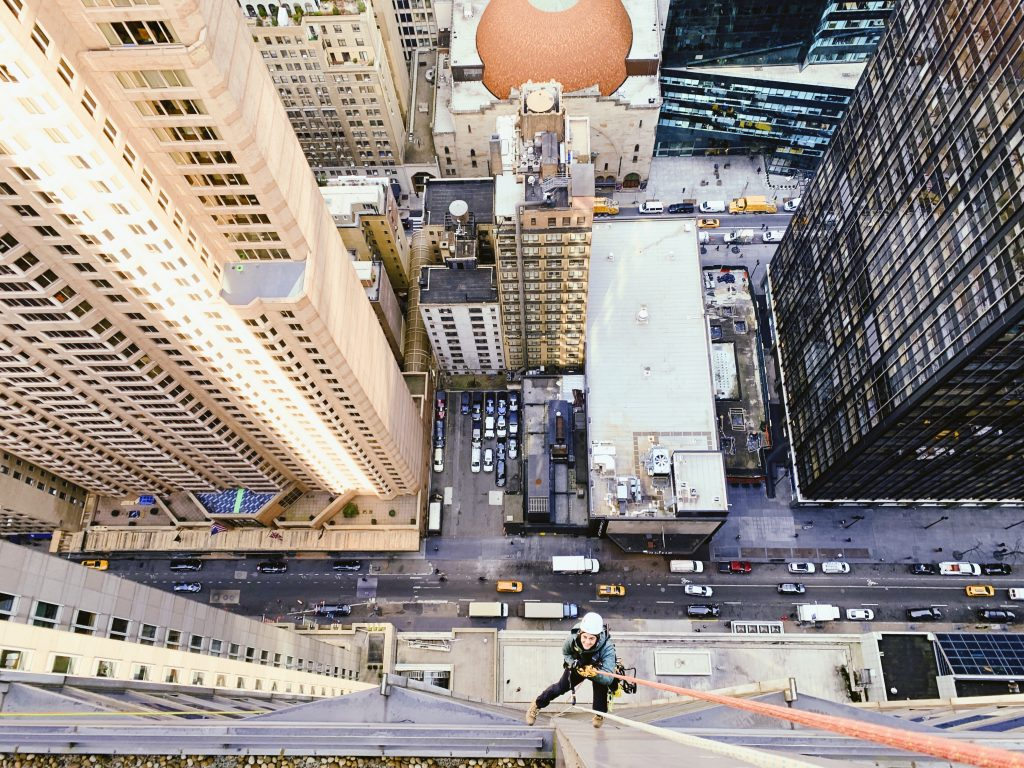 Bird's eye view of NYC, figure suspended from rope