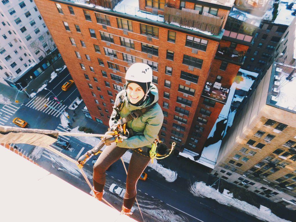 Woman in hardhat repels on rope off side of building, street far below.