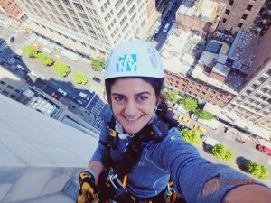 Selfie portrait of young woman in harness on side of building, street is very far below