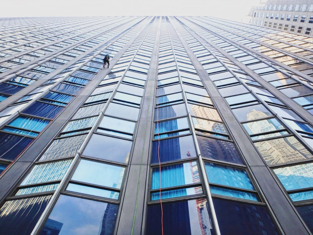 Geometric pattern of windows on building side, small figure repels down rope