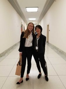 Two female MLA students smiling in hallway