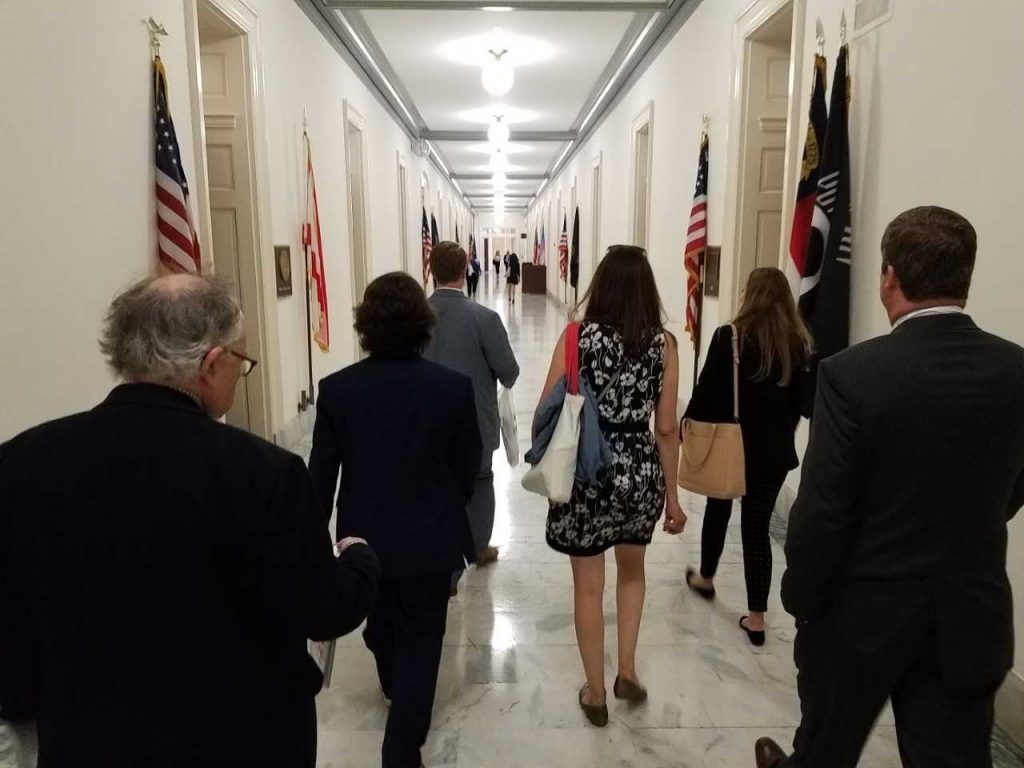 People walking in hallway with American flags along walls.