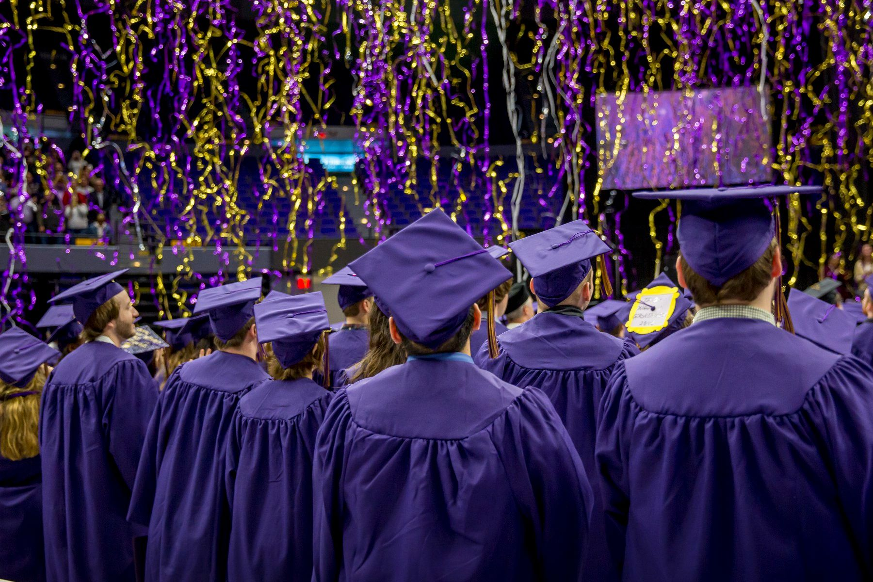 Graduates in caps and gowns, purple and gold streamers