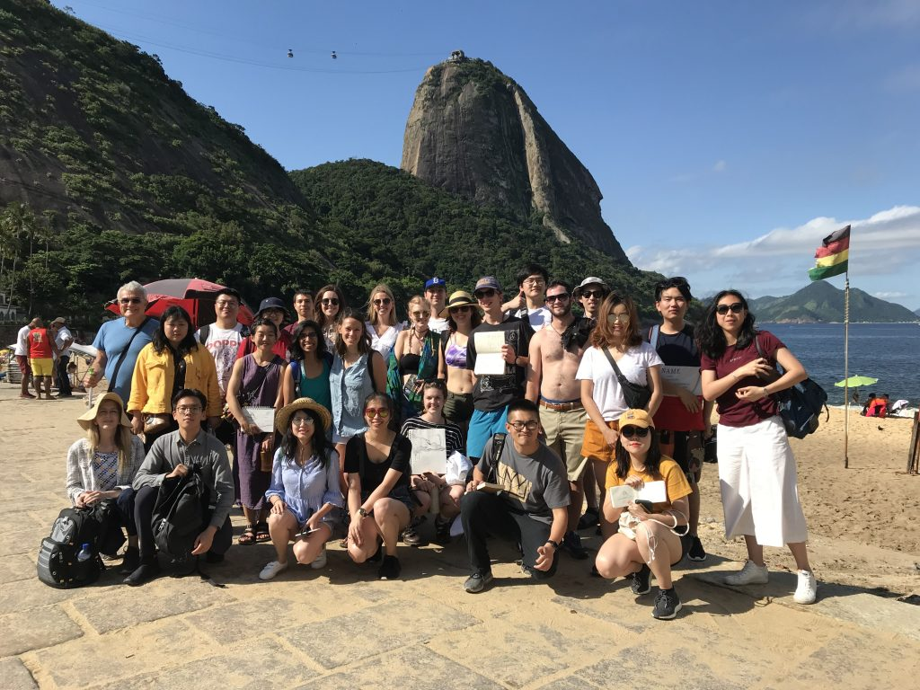 Smiling group on sunny beach, cliff with gondola in background