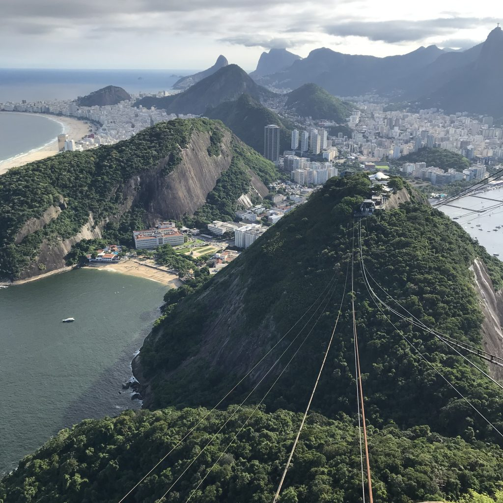 Cable lines suspend down mountain, view of city far below in the distance