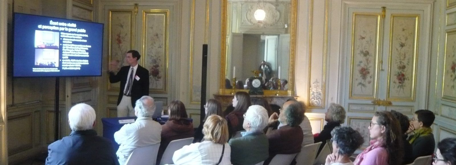 Professor gives talk in ornate French room