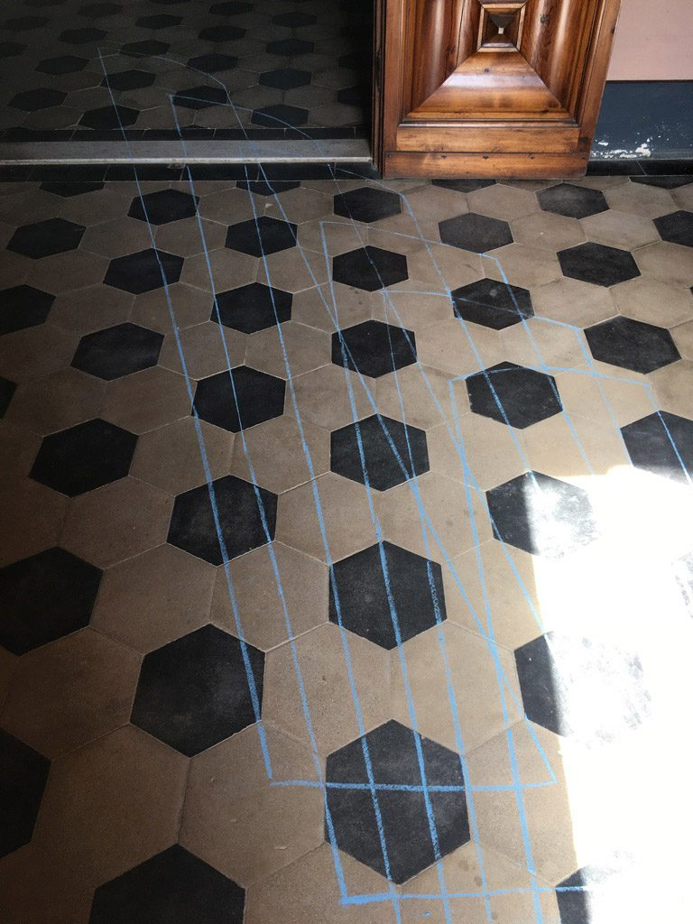 Light patterns and chalk drawn on tiled floor