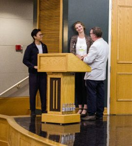 Young Asian man stands by podium on stage
