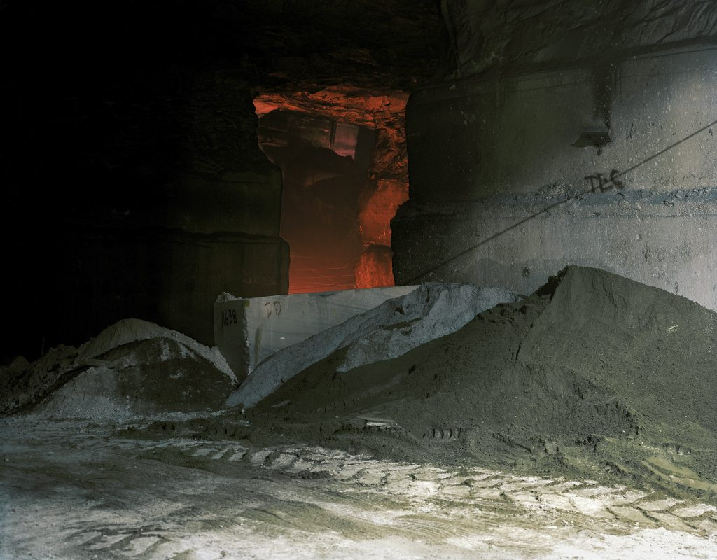 Cave with glowing red entryway in dark rock