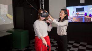 Professor adjusts headset on student's face