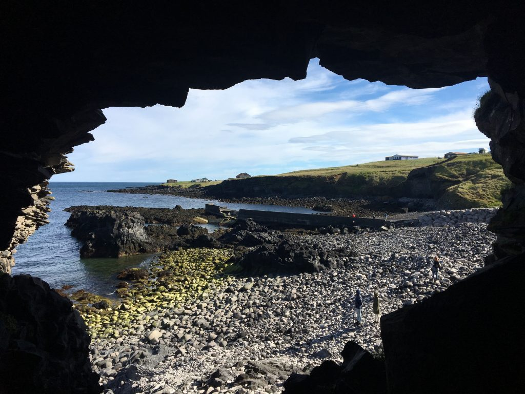 view of rocky coast through cave hole