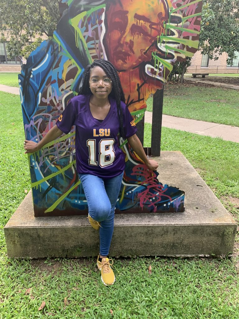 Female student in purple football jersey by colorful sculpture