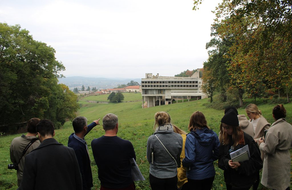 students and professors on green grass in countryside