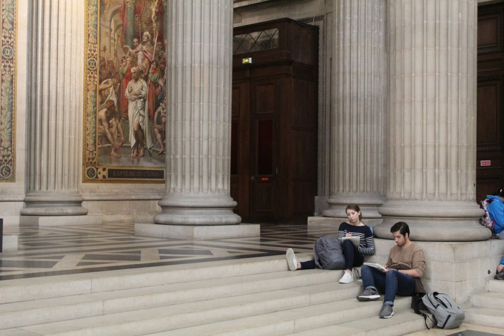 students sitting on steps by columns