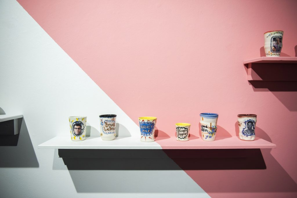 Shelf of mugs, pink and white wall
