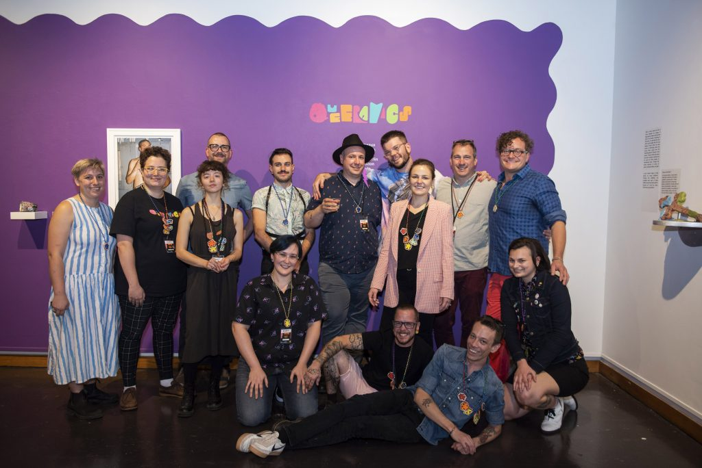 group in front of Queeramics exhibition sign