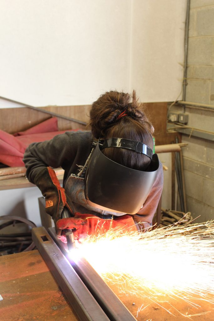 Girl welding with mask, shooting sparks