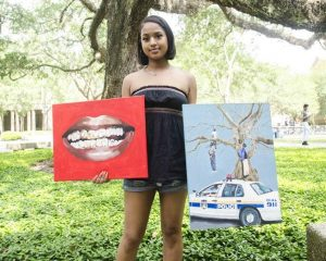 Chayse Sampy holding paintings
