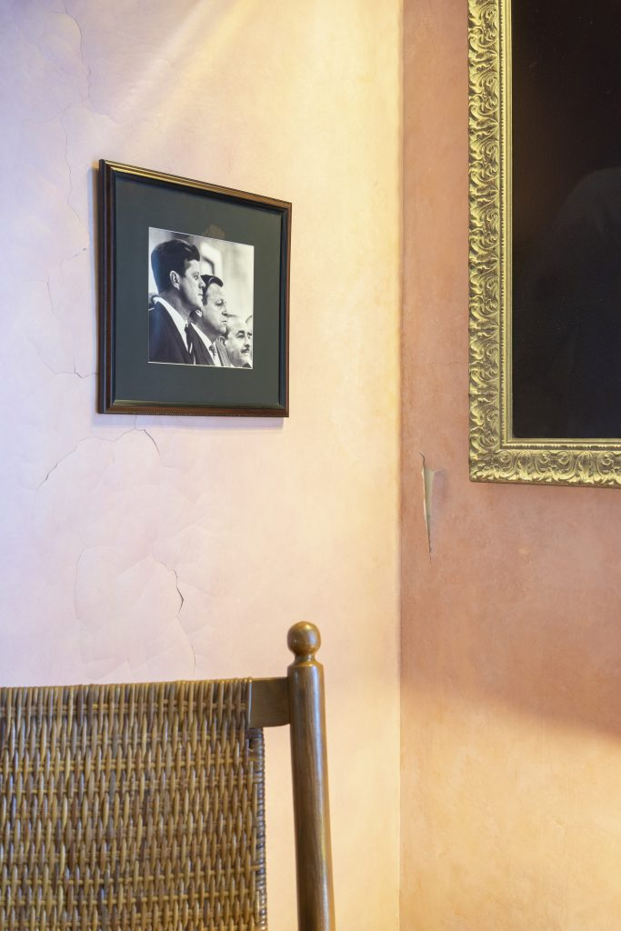 Photo of room interior: peach walls, framed photo of JFK