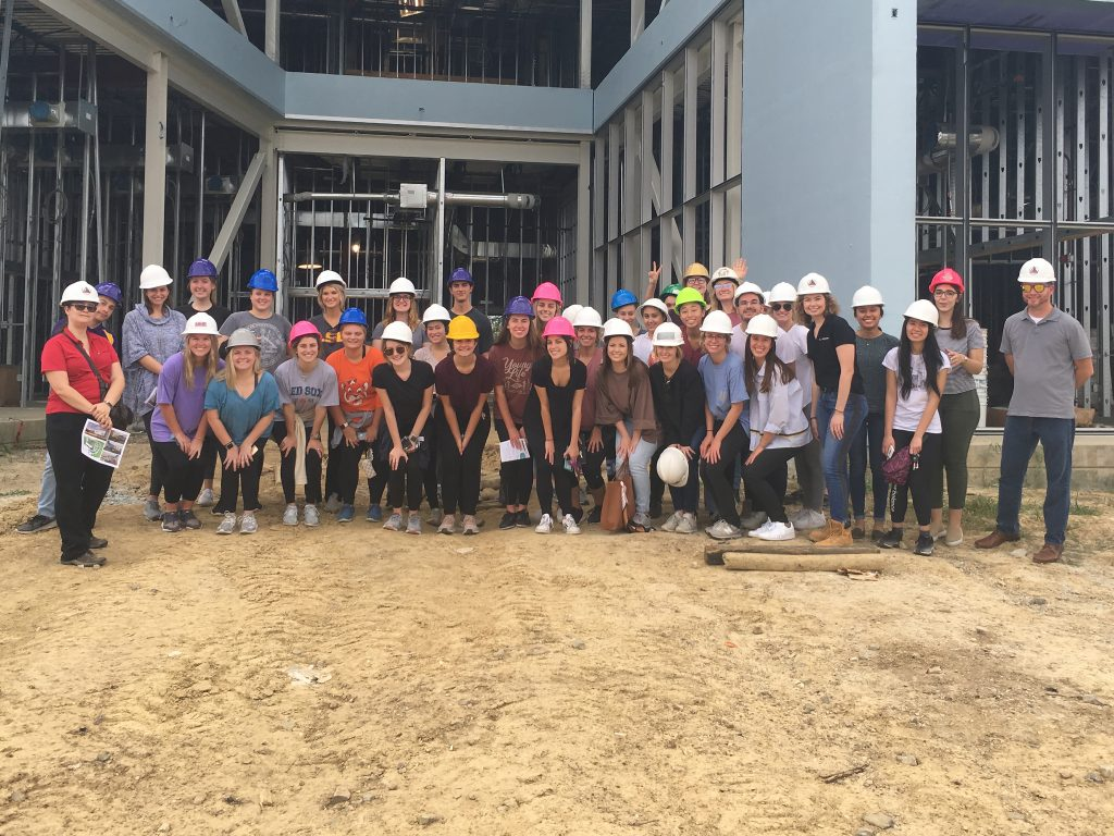 Group of students wearing hardhats in front of construction site.