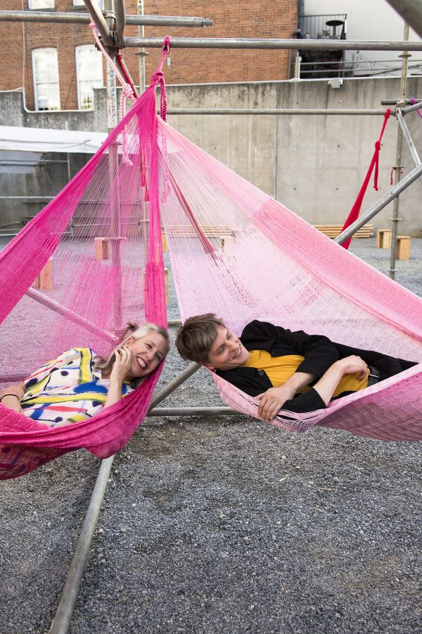 Woman and man in hot pink hammocks