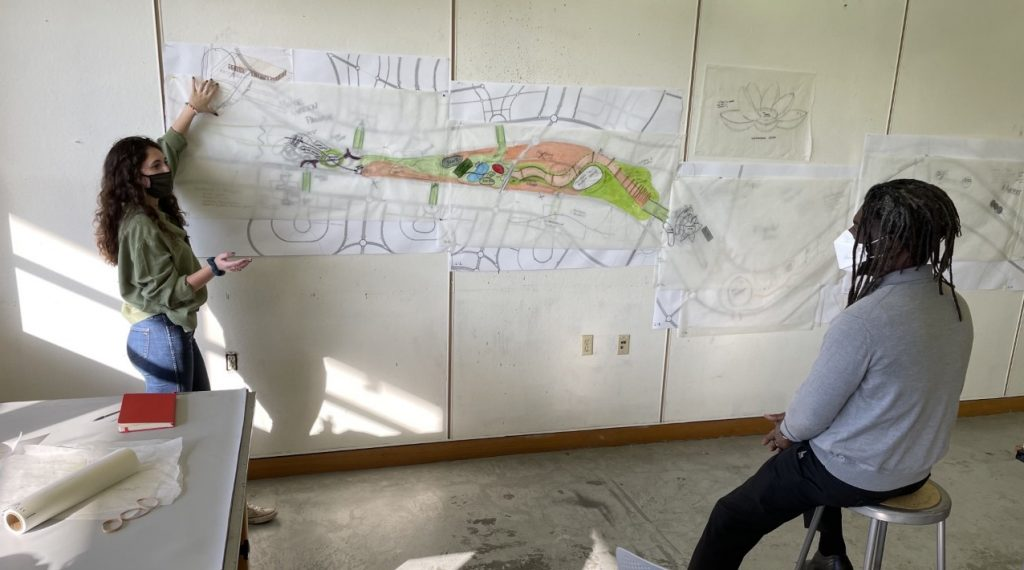 Student presents design on wall