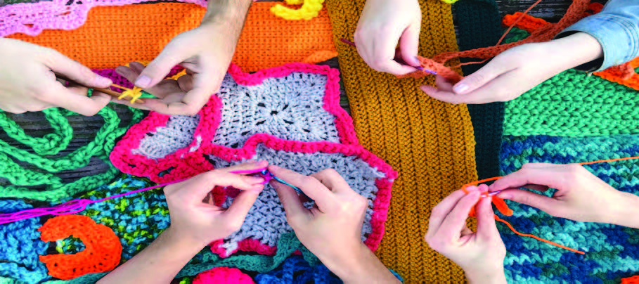 Hands knitting bright yarn