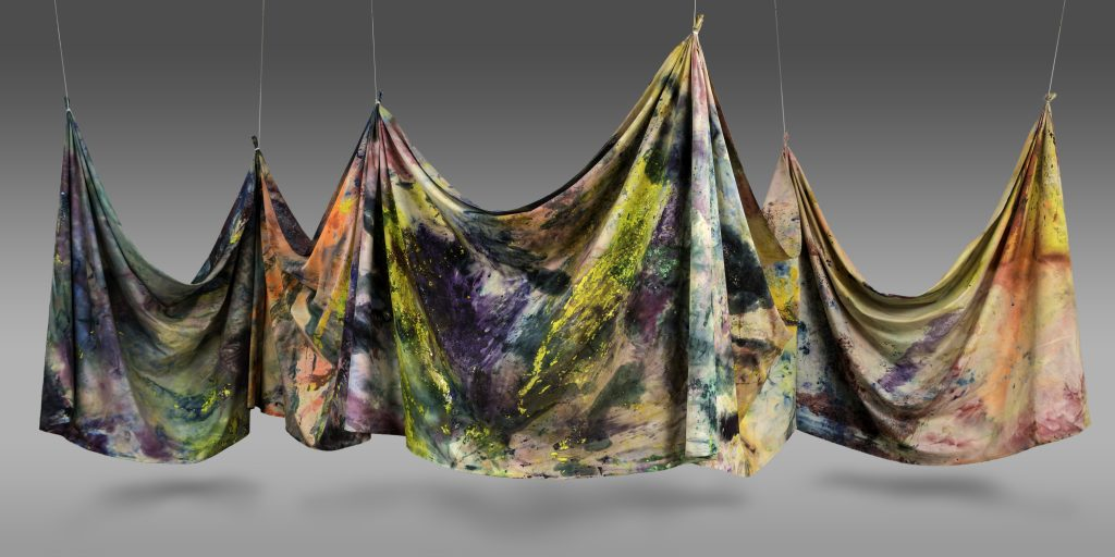 Hanging canvas suspended, colorful splattered paint on cloth