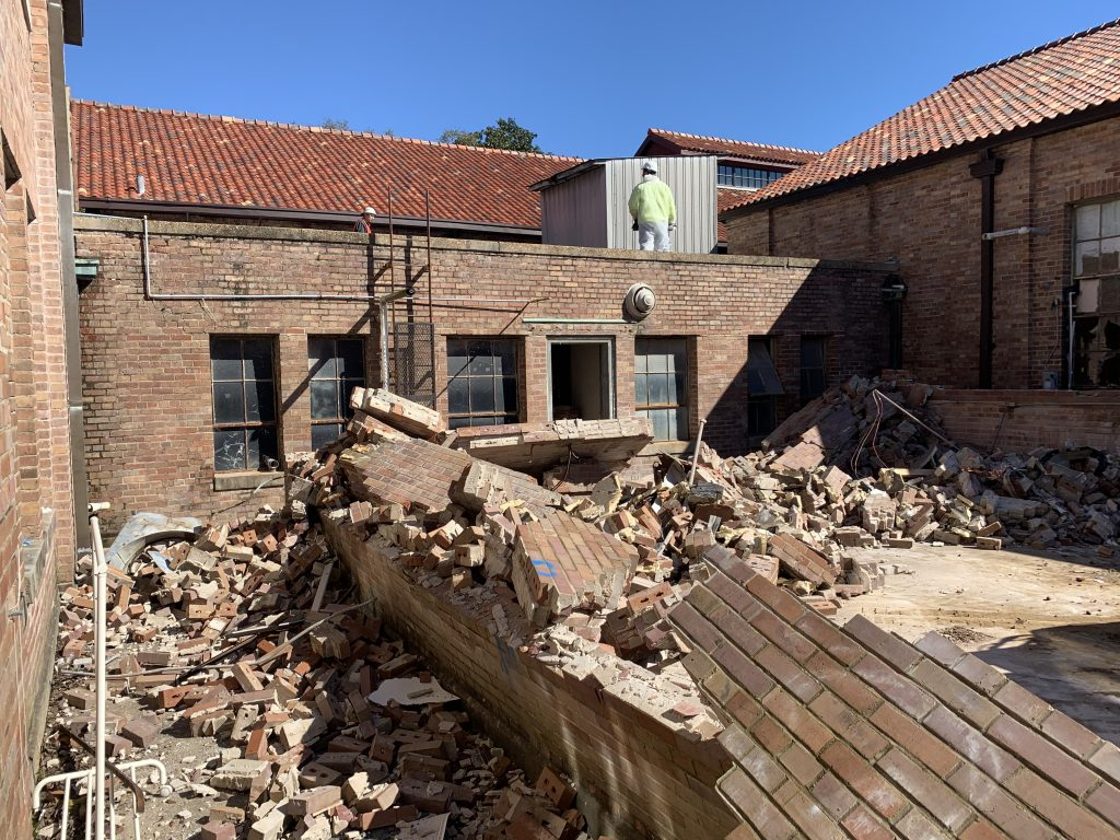 Demolition by red brick building