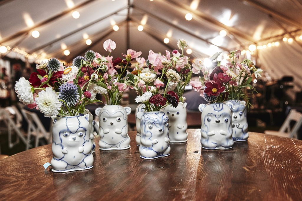 White vases shaped like animal creatures, filled with bunches of colorful wildflowers