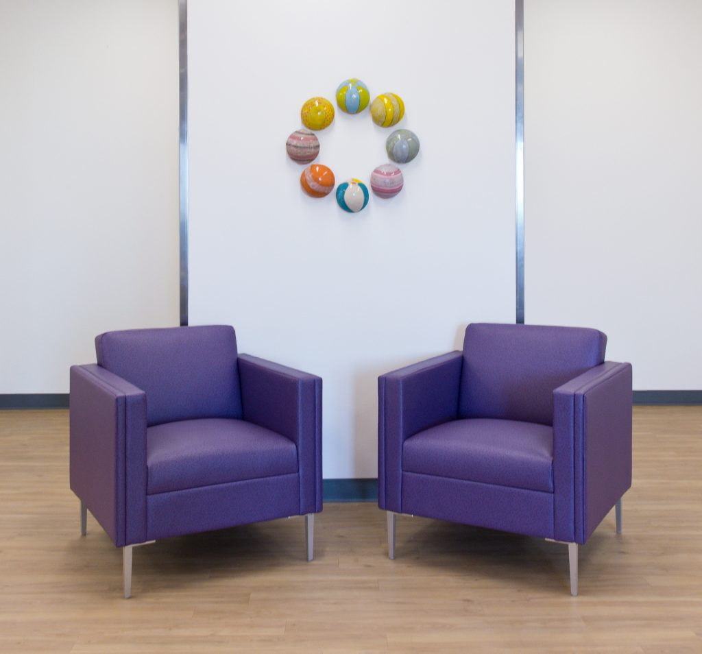 Ceramic spheres on white wall by purple chairs