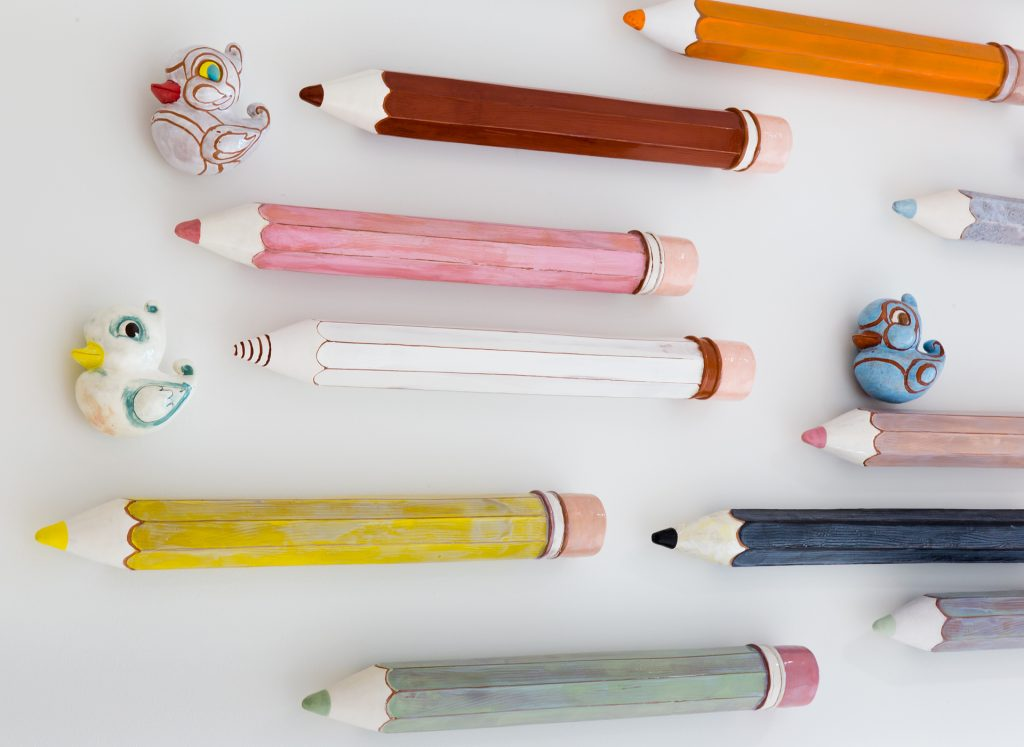 Large ceramic colored pencils on white wall