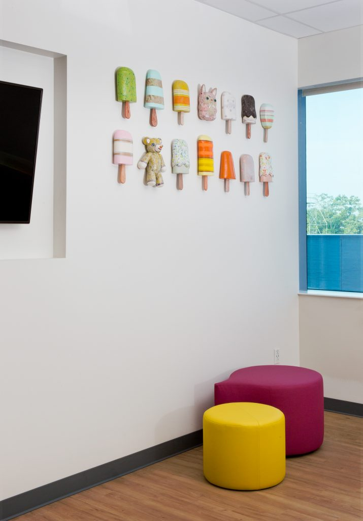 Ceramic popsicles and animals on wall