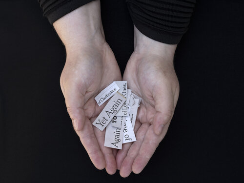 Hand holding pieces of paper with text