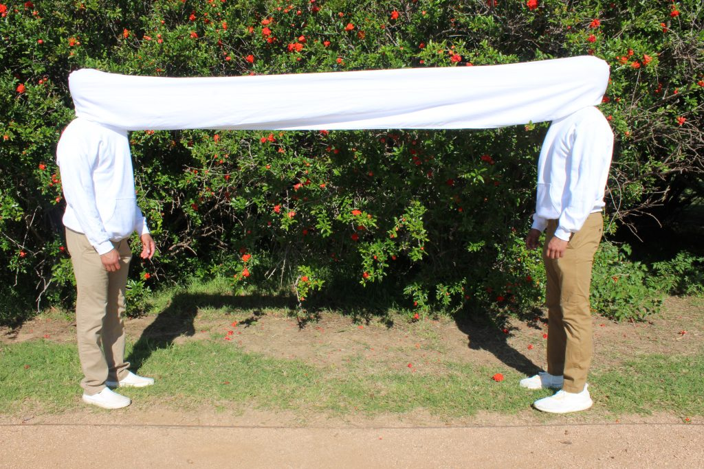 White cloth suspended across two men's heads.